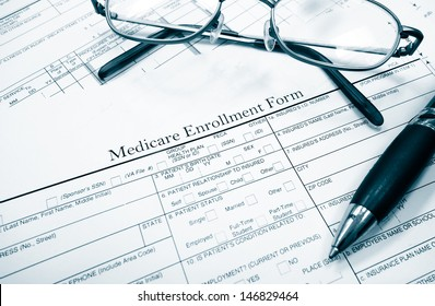 Medicare insurance form with glasses and pen