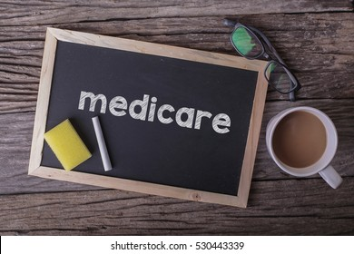 Medicare On blackboard with cup of coffee, with glasses on wooden background
