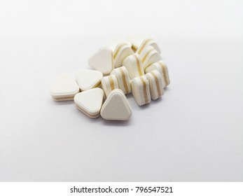 Medication concept. Many triangle white pills are antacids, used for relief stomachache and reduce flatulence. Focus on foreground, isolated on white background and copy space.