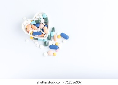 Medication of the cup with white heart, Colorful medicine, Medicine and capsules on over white background. Top view