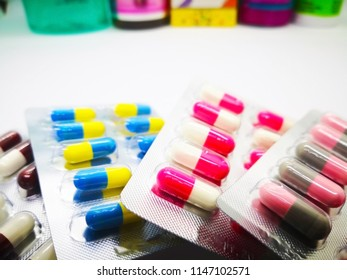 Medication and healthcare concept. Heap of colorful capsules medicine in silver blisters and colorful medicine bottles. Isolated on white background, selective focus and copy space.