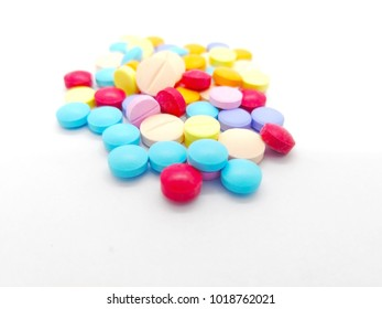 Medication and healthcare concept. Many colorful tablets of drug. isolated on white background, used to treat symtoms or diseases. Selective focus and copy space.