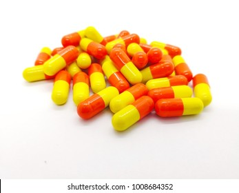 Medication and healthcare concept. Many orange-yellow capsules of Tetracycline 250 mg. isolated on white background, used to treat many different bacterial infections. Focus on foreground .