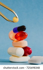 Medication management and pharmaceutical care and balancing risk and benefit with polypharmay; many pills balanced on top of each other as a tower