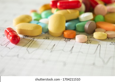 Medications with drugs for medical treatments. Medicines for legal use in humans. Drugs on EKG paper. Selective focus.