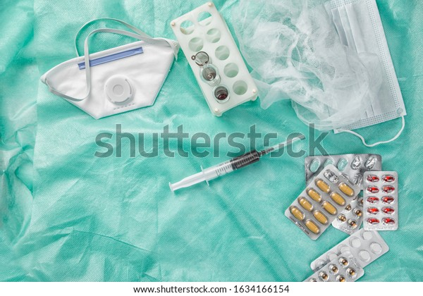 medications in packages, disposable medical masks, and blood samples in a syringe . on a medical green background