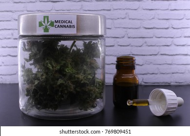 Medicinal cannabis buds and marijuana oil on a black table and with a white background
