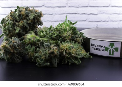 Medicinal cannabis buds in pot for muscle aches on a black table and with a white background