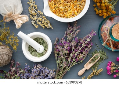 Medicinal herbs, mortar of healing herbs, sachet and bottle of drugs on wooden table. Herbal medicine. Top view, flat lay.