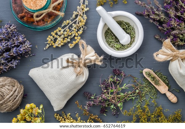 Medicinal herbs, mortar of healing herbs, sachet and bottle of healthy drugs on wooden table. Herbal medicine. Top view, flat lay.