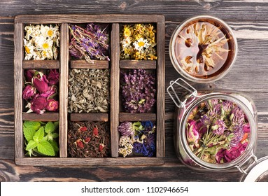Medicinal herbs in a wooden box and a glass jar for herbal tea and tinctures. Herbal medicine, health, healing