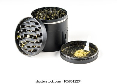 Medicinal marijuana against a white background. Black grinder open with Keef and Keef scraper
