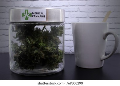 Medicinal marijuana buds and cannabis drink on a black table and with a white background