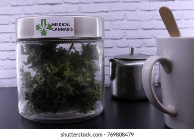 Medicinal marijuana buds and cannabis infusion on a black table and with a white background