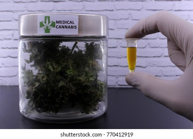 Medicinal marijuana buds and cannabis oil on a black table and with a white background