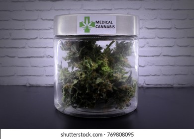 Medicinal marijuana buds in glass jar on a black table and with a white background