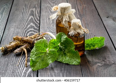 Medicinal plant - a burdock. The roots and leaves, oil in bottles on a wooden background. It is used for the treatment and care of hair