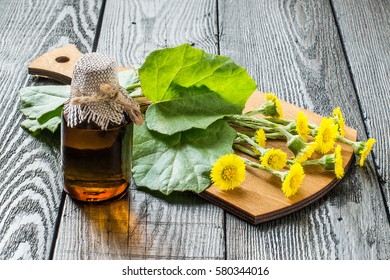 Medicinal plant coltsfoot (Tussilago farfara). The infusion, leaves and flowers on a cutting board. Dark wood background, selective focus
