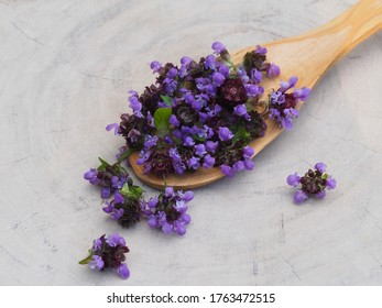 Medicinal plant Prunella vulgaris with blue flowers in a wooden spoon on a white stand closeup, top view. Useful herb for use in cosmetology and alternative medicine
