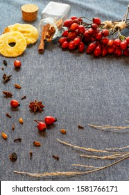 Medicinal plants and herbs composition. Bouquet of rosehips, pink branch, dried pineapple, cinnamon, dried goji berries, anise star on a light wooden background. Vertical frame, free copy space.