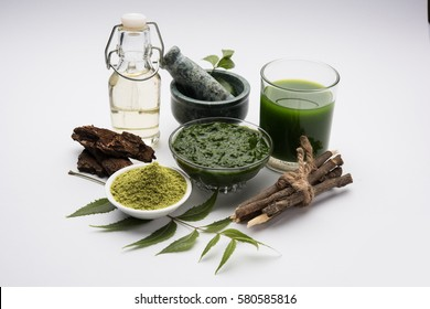 Medicinal/Ayurvedic Azadirachta indica or Neem leaves in mortar and pestle with lilac paste, juice and twigs, powder and oil, selective focus
