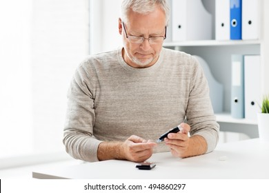 medicine, age, diabetes, health care and old people concept - senior man with glucometer checking blood sugar level at home