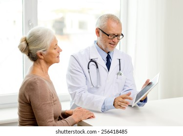 medicine, age, health care and people concept - smiling senior woman and doctor with tablet pc computer meeting in medical office
