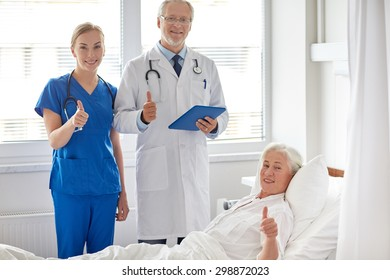 medicine, age, health care and people concept - doctor and nurse with tablet pc computer visiting senior patient woman and showing thumbs up at hospital ward
