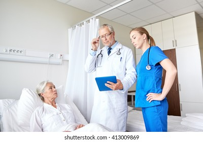 medicine, age, health care and people concept - doctor and nurse with tablet pc computer visiting senior patient woman at hospital ward