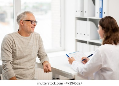 medicine, age, health care and people concept - happy senior man and doctor with clipboard meeting and talking in medical office at hospital