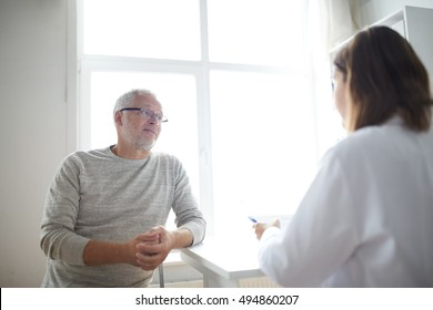 medicine, age, health care and people concept - senior man and doctor meeting in medical office at hospital