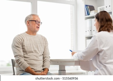 medicine, age, health care and people concept - senior man and doctor with clipboard meeting and talking in medical office at hospital