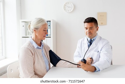 medicine, age, healthcare and people concept - senior woman patient and doctor with tonometer measuring blood pressure at hospital