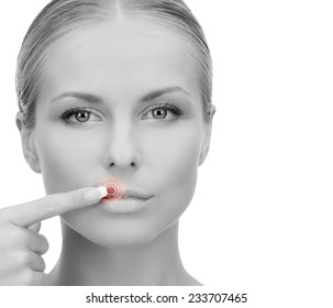 medicine, beauty, people and health concept - beautiful young woman pointing finger to her lips over white background