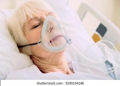 Medicine is the best medicine. Ill senior woman lying in a hospital bed while wearing an oxygen mask and undergoing treatment.