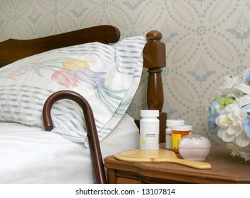 medicine bottles and a cane against a bed for an elderly person