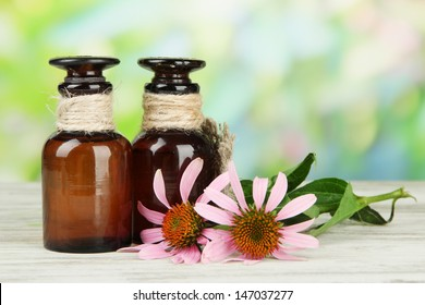 Medicine bottles with purple echinacea flowers on wooden table, outdoors