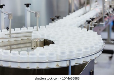 Medicine bottles transfer on line conveyor in pharmaceutical industry. Industrial Machine for quality of medical product in line conveyor processing. Industrial and factory technology concept.