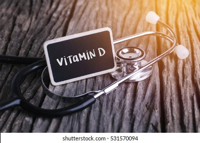 Medicine concept. Blackboard with word vitamin d on wooden background