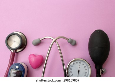 Medicine concept - stethoscope, blood pressure equipment, heart and pulse oximetere on pink background