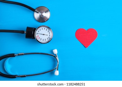 Medicine concept. Tonometer, stethoscope and heart on a blue background. Measurement of blood pressure.