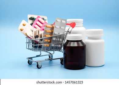 Medicine concept. Various capsules, pack of medicines in shop trolley with medicine bottles on a blue background, Pills concept, Buy and shopping medicine.