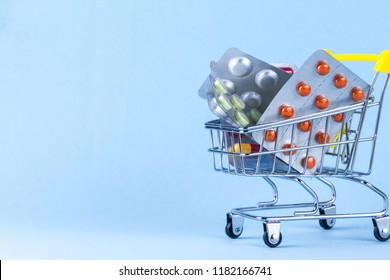 Medicine concept. Various capsules, tablets and medicine in shop trolley on a blue background. Pills concept. Buy medicine