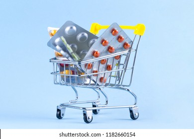 Medicine concept. Various capsules, tablets and medicine in shop trolley on a blue background. Pills concept. Buy medicine. Copy space
