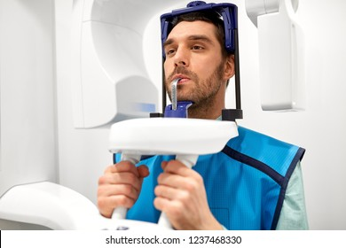 medicine, dentistry and healthcare concept - male patient having panoramic x-ray scanning procedure at dental clinic