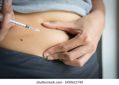 Medicine for diabetes disease of health care and self-care concept. Close-up of woman with syringe making insulin injections at abdominal skin (intra subcutaneous) for hyperglycemia by herself.