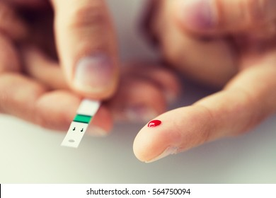 medicine, diabetes, glycemia, health care and people concept - close up of male finger with blood drop and test stripe