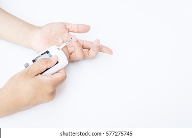 Medicine, Diabetes, Glycemia, Health care and people concept - close up of male finger with blood drop and test stripe  to checking blood sugar level by Glucose meter on white background