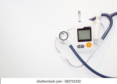 Medicine, Diabetes, Glycemia, Health care and people concept - close up of lancelet, Glucose meter and stethoscope on gray background.