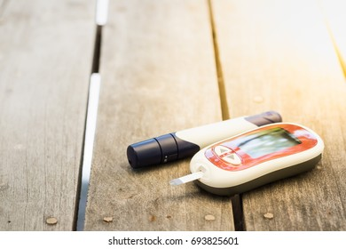 Medicine, diabetes, glycemia, health care and people concept - close up of Glucose meter and lancet for check blood sugar level on wooden table.